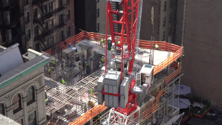 Construction Workers And Large Crane Work Hard To Build A New