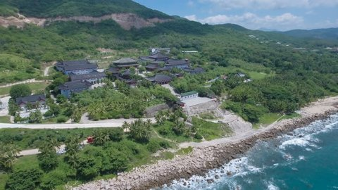 Aerial drone shot retreating from a Buddhist temple complex, located on the rugged beautiful coastline of Hainan island in the South China Sea.