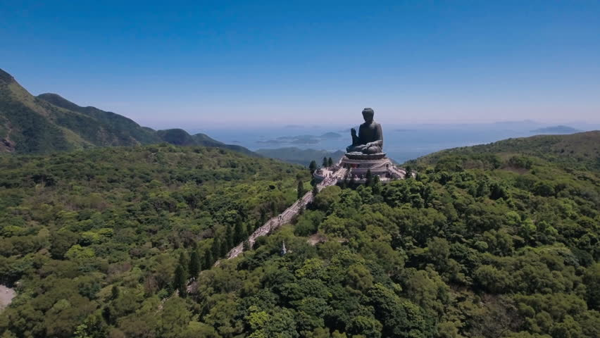 Aerial drone flight towards the peaceful Tian Tan bronze Buddha statue, part of the Po Lin monastery in Hong Kong, located in a beautiful mountain setting.