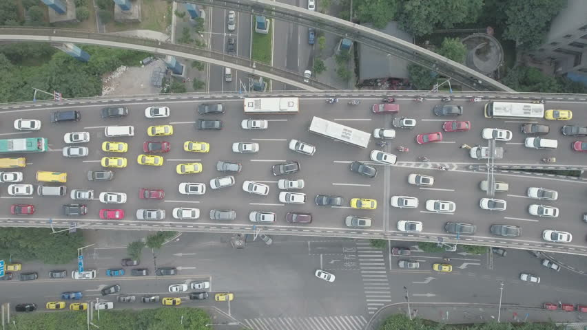 Yellow taxis and other traffic fight for space as two lanes merge on a highway in Chongqing, China. D-log profile DJI Phantom.