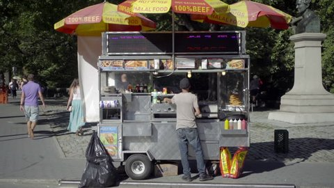 NEW YORK - SEPT 14, 2016: hot dog vendor at Columbus Circle by Central Park in summer NYC. Street food is a large part of food culture in the city.