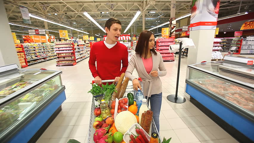 Cheerful couple walking through mall with a market trolley full of products | Shutterstock HD Video #1987417