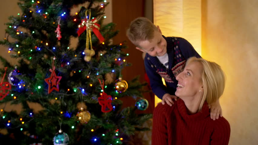 Happy blond mother with her son under a christmas tree. | Shutterstock HD Video #19876087