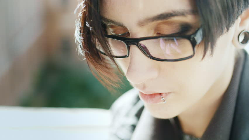Portrait of an attractive brunette with a pierced lip. She is wearing glasses, he uses a telephone. Hands with the phone are reflected in the glasses | Shutterstock HD Video #19895554