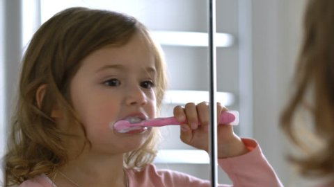 Little girl diligently brushing his teeth in the mirror.