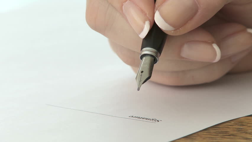 Woman signing signature with a fountain pen