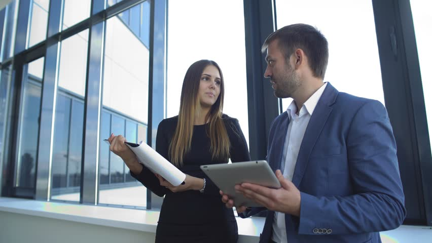 Businesswoman and businessman standing in office and discuss the business plan   Shutterstock HD Video #19920157