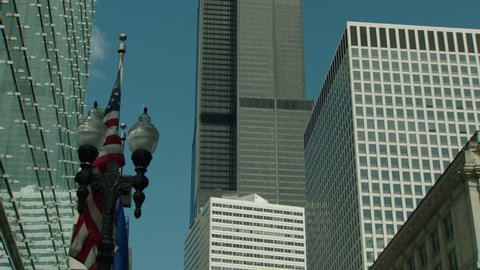 day hold up mid sections office buildings lamppost street American Flag, see airplane e background right left then tilt top Sears Tower Willis tower right, Chicago buildings