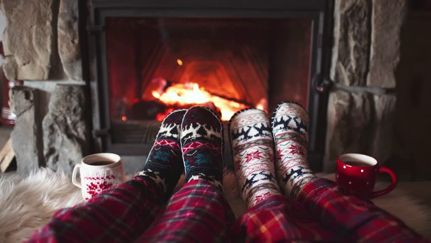 Feet in woollen socks by the Burning Christmas Cozy Fireplace. 4K. Couple relaxes by warm fire with cup of hot drink and warming up their feet. Winter and Christmas holidays concept. #19936057