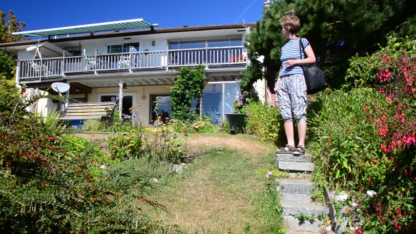 Middle age woman on trail with nice cottage view at summer day in Vancouver, Canada.