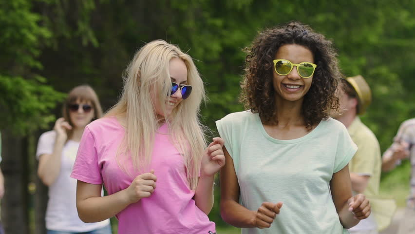 Couple of hot girls dancing with friends at open air festival, enjoying summer