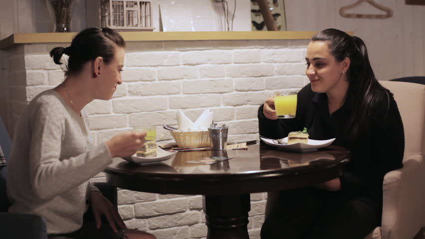 Two young women eating a cake, drinking a tea and talking in a cafe. Woomans have a positive mood, smiling and laughing - HD stock footage clip