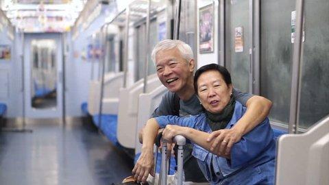 Asian Senior using public transportation to do retirement travel trip