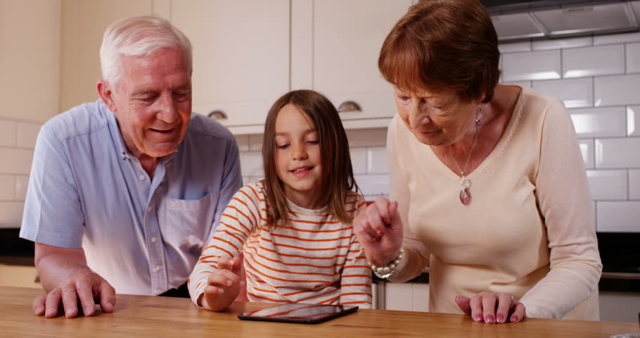 4k, Cute little girl showing her grandparent how to use a digital touchscreen tablet. | Shutterstock HD Video #20048212