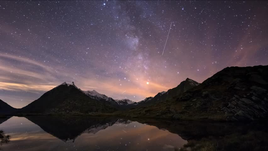 The apparent rotation of the Milky Way and the starry sky beyond snowcapped mountain ridge, reflected on idyllic apine lake. Orion Constellation coming from left at the end. Time Lapse 4k video.