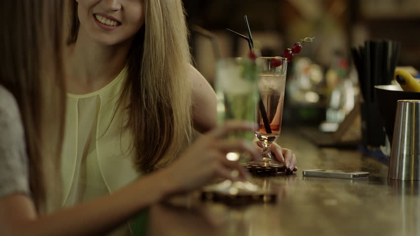 Women clinking glasses and enjoying cocktails | Shutterstock HD Video #20058997