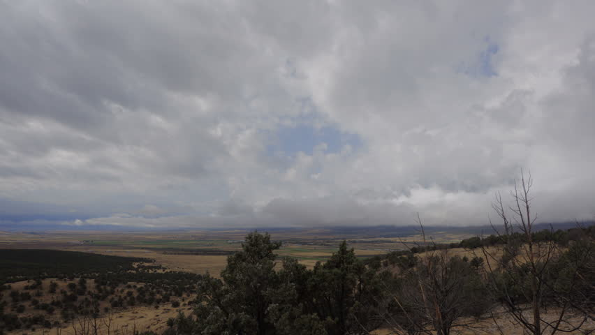 SANPETE COUNTY, UTAH - SEPTEMBER 2016: Time lapse-Low clouds moving over rural mountain valley on rainy overcast autumn day. Viewed looking down from high mountain ridge with juniper trees.