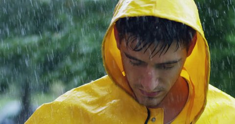 A man under the heavy rain, he looks up defiantly with a strong and nasty look up to the challenge. Sport concept, extreme, rain, fatigue, beauty.