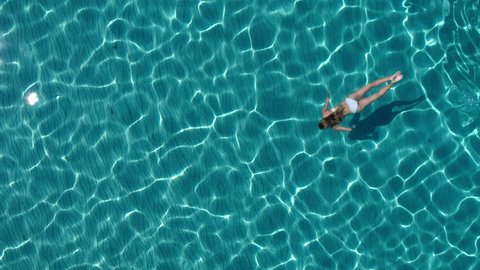 Aerial - Beautiful young woman with toned body swimming underwater in crystal clear water