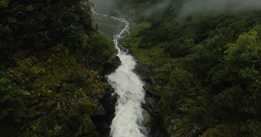Dramatic reveal of a huge mountain waterfall located near Geiranger Fjord, Norway