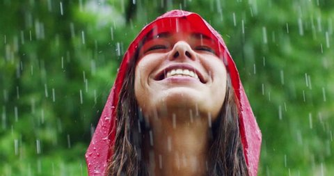 girl smiles and laughs in the rain. the rain falls, the drops fall on his face and the girl is happy with life and nature around. concept of nature and happy life. Adventure, purity.