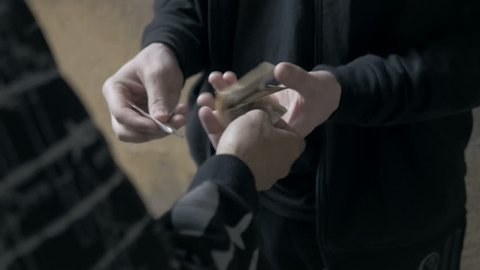 Close-up of criminal selling drugs to a drug addict. Suspicious young men having bad habits.