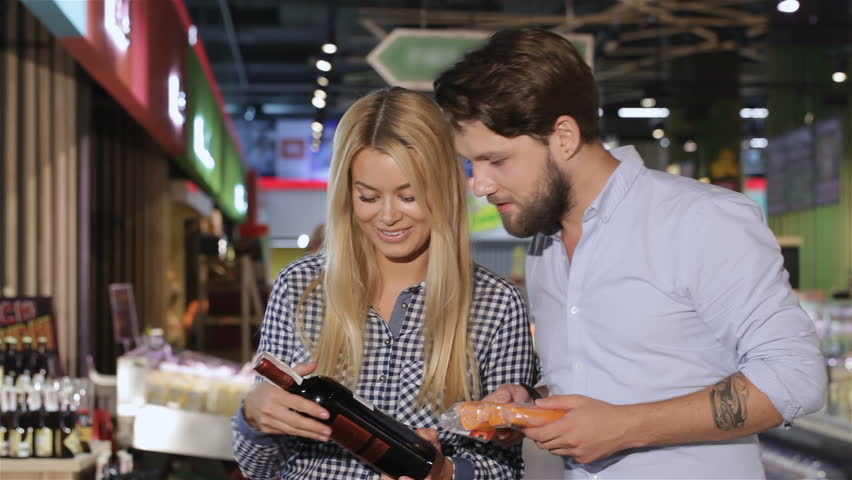Young attractive couple choosing wine at the supermarket. Handsome bearded man reading about the wine from the label. Pretty blond caucasian woman holding a bottle of wine in her hands