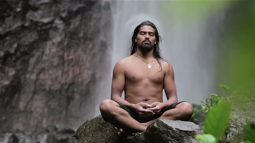 man doing sitting meditation at waterfall in the tropics