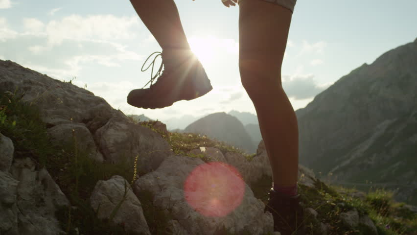 SLOW MOTION, CLOSE UP: Courageous female hiker climbing mountaintop, walking off trail on dangerous rough rocky mountain ledge. Steep wall opening beautiful view on high European Alps sunbathing | Shutterstock HD Video #20183842