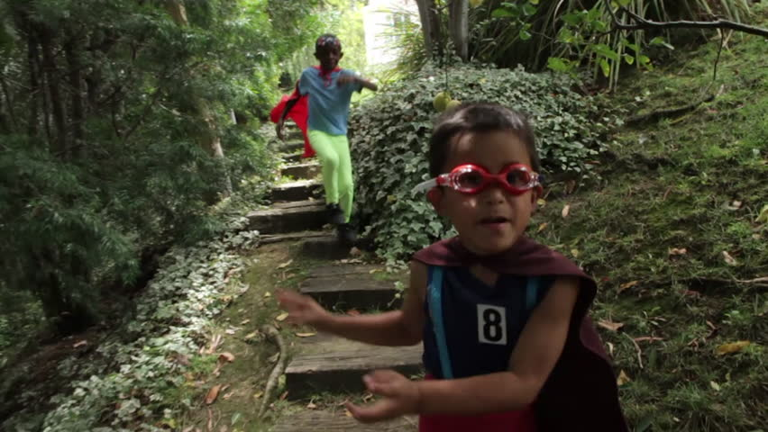 Two young boys dressed in homemade superhero costumes run through their backyard garden, jumping down stairs as they go. They through air punches and mimed energy blasts at the camera.