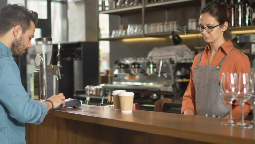 Handsome Young Man Paying for Takeaway Coffee with Credit Card at Coffee Shop. Shot on RED Cinema Camera in 4K (UHD).
