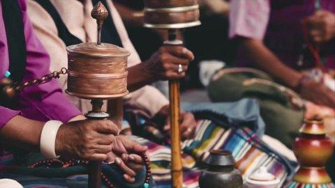 Buddhist prayer wheels, the ceremony at the temple. Women pilgrims twisting prayer wheels. Closeup. Boudhanath, Kathmandu, Nepal.
