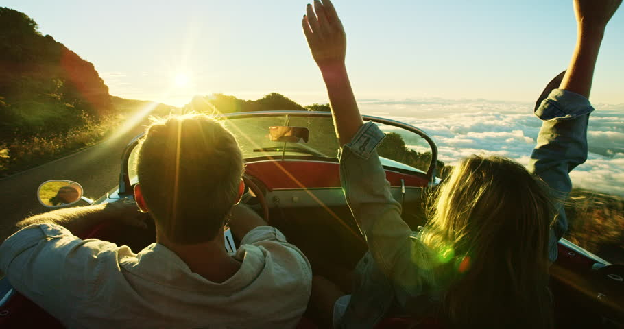 Happy couple driving on country road into the sunset in classic vintage sports car   Shutterstock HD Video #20219053
