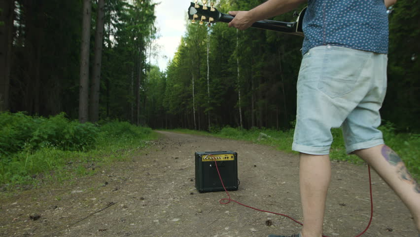 Man is playing at the electric guitar in forest | Shutterstock HD Video #20234134