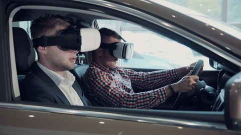 Instructor and man in glasses to pass virtual exam for driver license using virtual reality glasses.