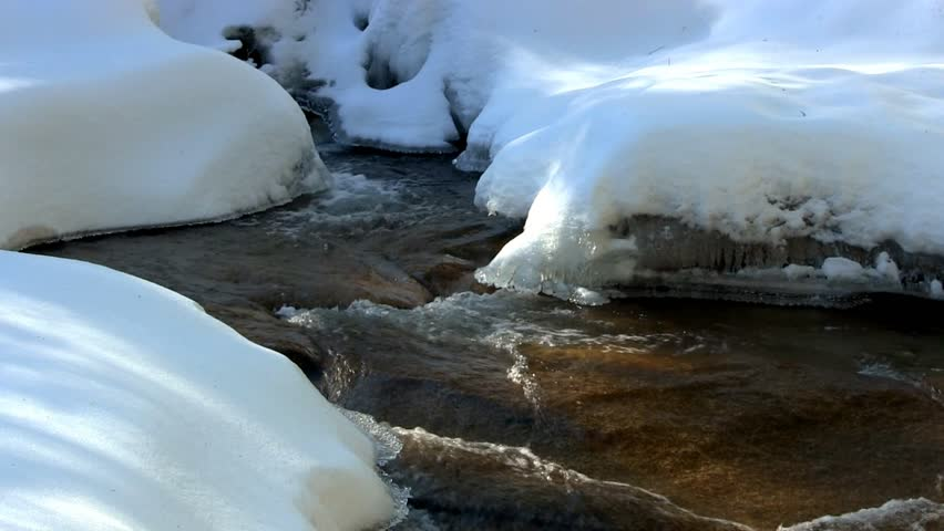 A beautiful crystal clear river flows at Diane's bath in Bartlett, New Hampshire.  The moving water forms interesting shapes as it carves a path through the pristine ice and snow of winter.