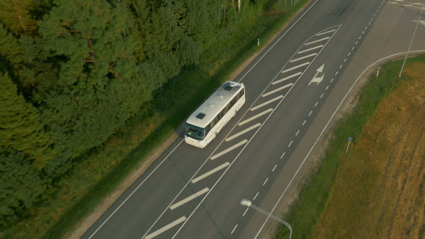 Aerial Shot of Tourist Bus Driving on Highway Surrounder by Forest