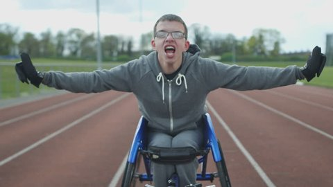 4K Portrait of young disabled athlete in racing wheelchair at sports track. Shot on RED Epic.