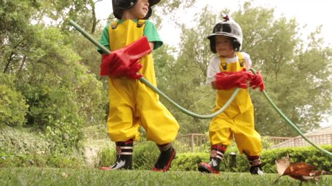 Two young boys dressed in homemade firefighter costumes march across their suburban backyard, carrying a garden hose while playing make believe.