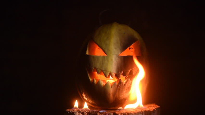 Scary carved halloween pumpkin in hot burning hell fire flames. The big helloween pumpkin has a mad face with glowing eyes and also a glow in its mouth and teeth.