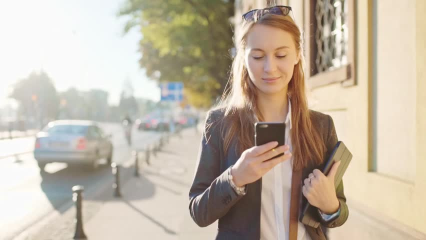 Young Businesswoman Using SmartPhone, Going to Work in the Sunny Morning City. SLOW MOTION. STEADICAM Stabilized Shot. Attractive Professional Business Woman with a cell phone in a city. Lens Flare.
