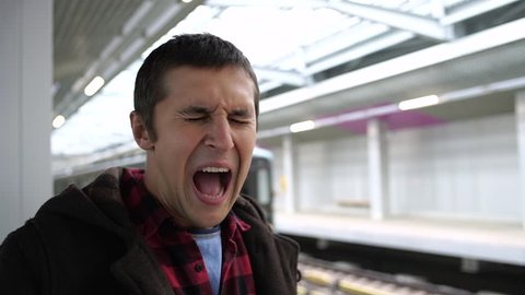Young man with noise blocking safety acoustic earmuffs grimacing from loud noises in background of arriving subway train. Slow motion
