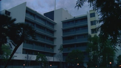 day late day, dusk across an left shaped 6 story white medical building hospital, dark windows, palms, lampposts on, overcast s then see 2 male doctors from rfg l can time night