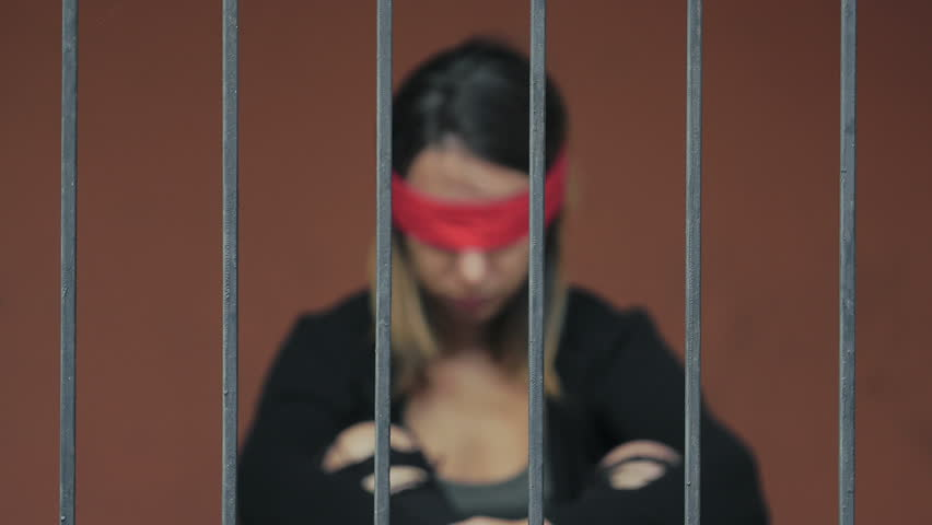 young woman kidnapped and imprisoned in a cell, blindfolded