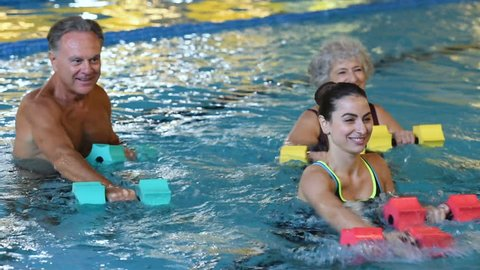 Happy active fitness mature man and senior woman doing exercise with aqua dumbbell in a swimming pool with instructor. Retired people doing aqua gym exercise with water dumbbell.