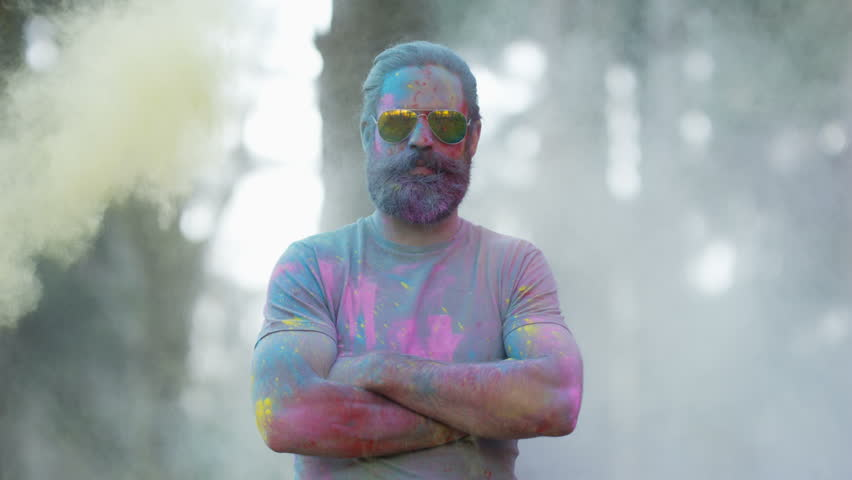 4K Portrait of serious hipster guy standing still while being covered in coloured powder at festival. Shot on RED Epic. | Shutterstock HD Video #20370667