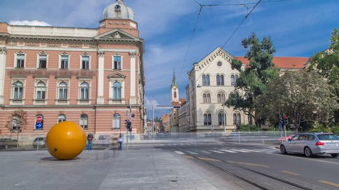 Street and orange ball near new building of Croatian Music Academy timelapse in Zagreb, Croatia. Traffic on the road with trams, blue cloudy sky at sunny day