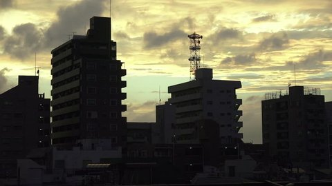 Clouds Pass Over Silhouetted Apartment Building In Tokyo At Sunset, Arakawa City, Tokyo, Japan  July 12th, 2014