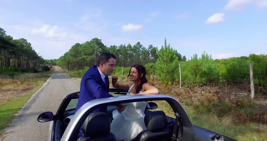 Happy wedding couple standing in a convertible car  | Shutterstock HD Video #20446627