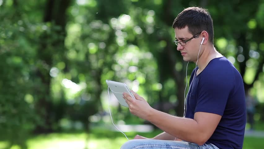 Man sits on the bench in city park and communicates via tablet computer. Adult man in blue t-shirt sits on bench in public garden and speaks on tablet pc. Man with tablet pc communicates through skype